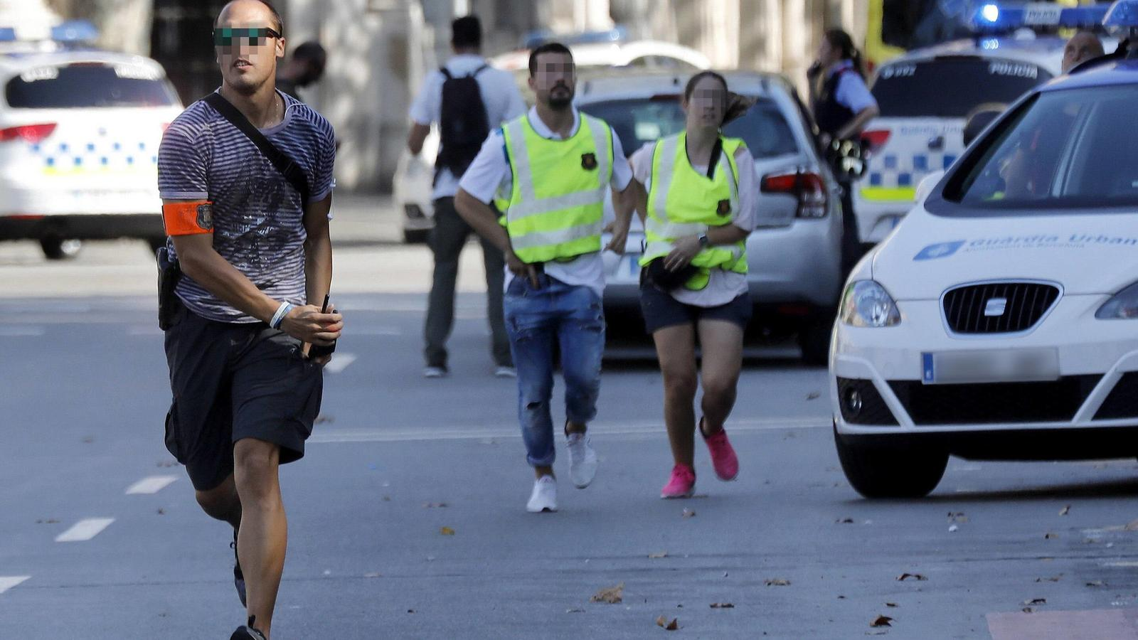 Mossos d Esquadra Police officers and emergency service workers set up a security perimeter near the site where a van crashes into pedestrians in Las Ramblas, downtown Barcelona, northeaster Spain, 17 August 2017. The number of people injured and the