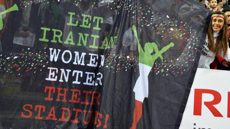 """Eine iranische Frau zeigt ihre Forderung auf einem Banner: """"Lasst iranische Frauen ihre Stadien besuchen!"""""""