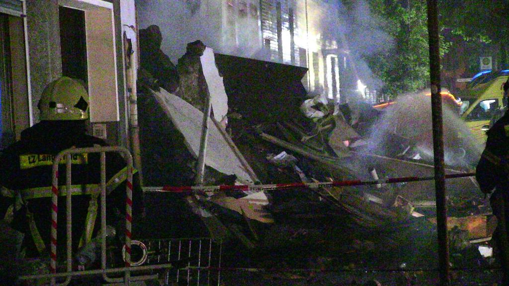 24.06.2018, Nordrhein-Westfalen, Wuppertal: Feuerwehrmänner stehen vor Trümmern eines Wohnhauses. Bei einer Explosion in dem Gebäude sind 24 Menschen verletzt worden. Foto: Gianni Gattus/Blaulicht Solingen/dpa +++ dpa-Bildfunk +++
