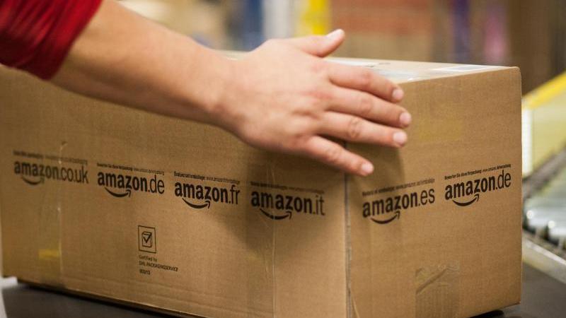 Ein Mitarbeiter von Amazon greift im Amazon Logistikzentrum nach einem Paket, das über ein Laufband fährt. Foto: Christoph Schmidt/Archiv