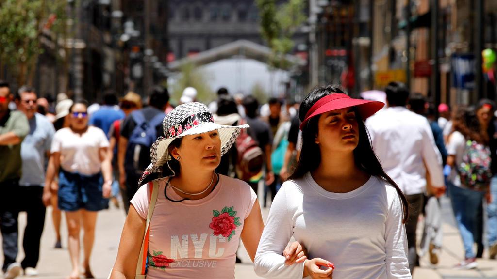 """31.05.2018, Mexiko, Mexiko-Stadt: Zwei Frauen spazieren durch den Zentrum der mexikanischen Hauptstadt. Da die Stadt auf 2250 Metern Höhe liegt, ist die Sonne dort besonders intensiv. (zu dpa-Korr """"Sombreros, Hydranten, Feuchttücher - weltweite Strat"""