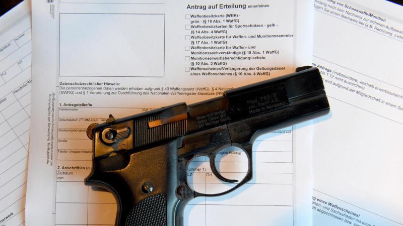 Eine Pistole liegt auf einem Antrag für die Ausstellung eines Waffenscheines. Foto: Carsten Rehder/Archiv