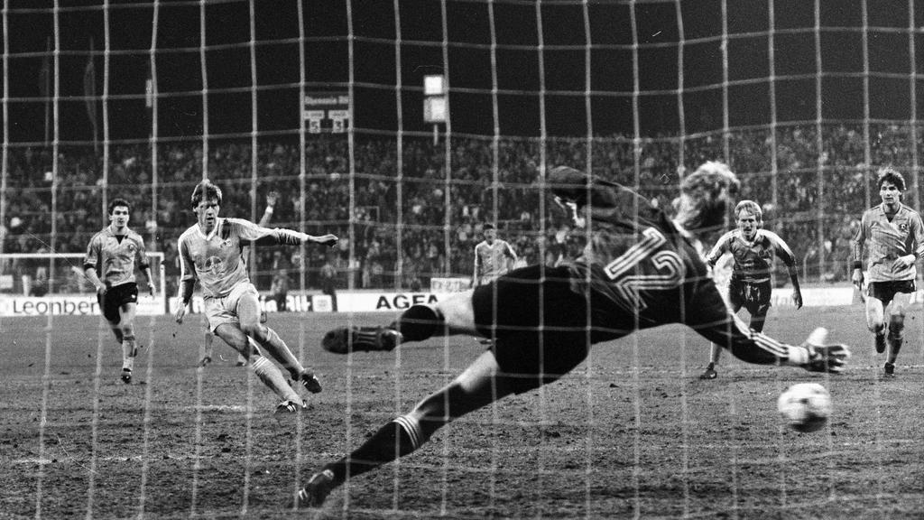 Uefa-Cup: Bayer 05 Uerdingen - Dynamo Dresden (7:3/19.3.1986). Wolfgang Funkel (Uerd.) verwandelt Elfmeter zum 6:3 gegen Torwart Jens Rammer (Dresden). HMUEFA Cup Bayer 05 Uerdingen Dynamo Dresden 7 3 19 3 1986 Wolfgang Funkel  transforms Penalty to
