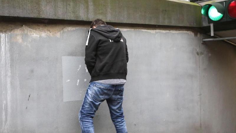 Ein junger Mann steht an einer Wand