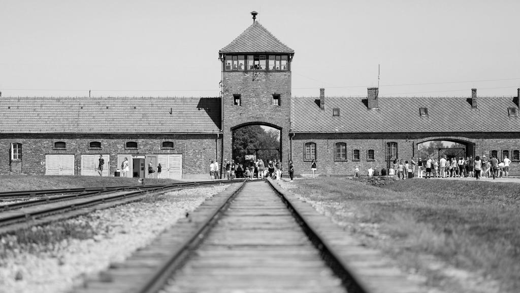 Besucher gehen vor dem historischen Tor (Innenneite) durch das frühere Vernichtungsslager Auschwitz-Birkenau.