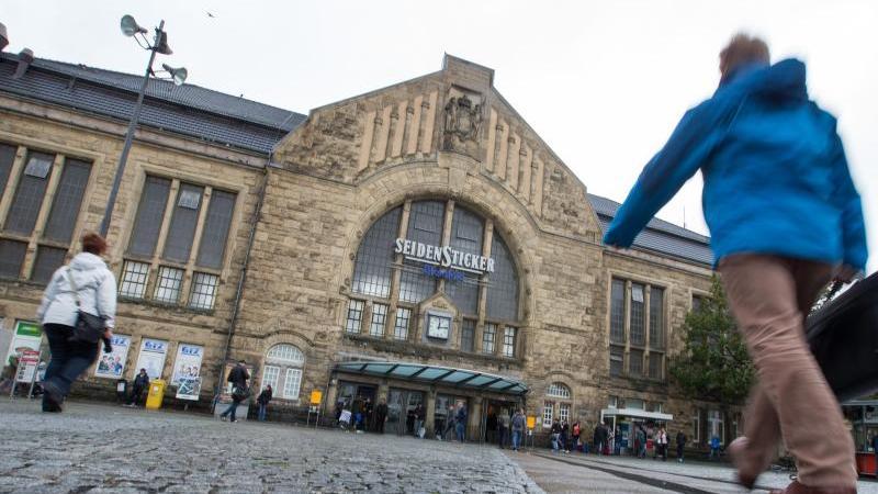 Reisende gehen über den Vorplatz vom Hauptbahnhof in Bielefeld (Nordrhein-Westfalen). Foto: Friso Gentsch/Archiv