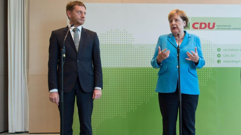 """Bundeskanzlerin Angela Merkel und der sächsische Ministerpräsident Michael Kretschmer bei einer Veranstaltung in Dresden im August. Merkel schließt eine Koalition mit der AfD nach der Landtagswahl in Sachsen """"kategorisch"""" aus. Foto: Sebastian Kahnert"""
