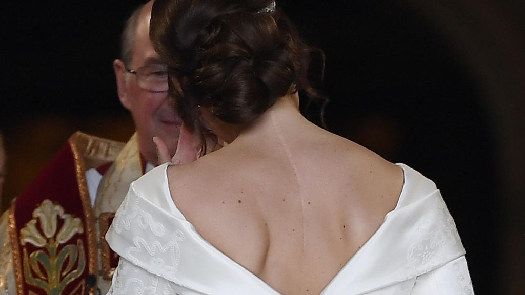 12.10.2018, Großbritannien, Windsor: Die Braut, Prinzessin Eugenie kommt in Begleitung ihres Vaters zu ihrer Hochzeit an der St.-Georges-Kapelle von Schloss Windsor an. Am Rücken ist eine Narbe von einer Skoliose-Operation im Alter von 12 Jahren sich