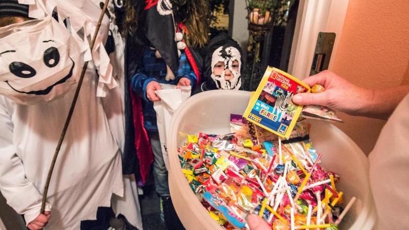 Kinder in Kostümen bekommen an einem Hauseingang Süßigkeiten. Foto: Armin Weigel/Illustration