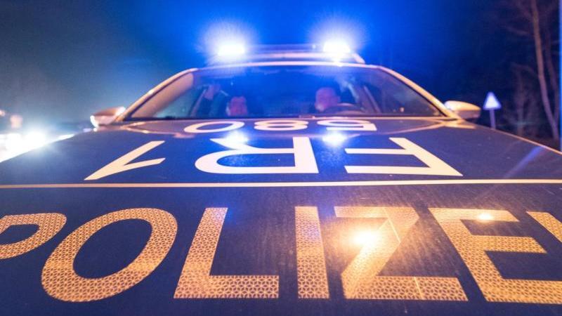 Ein Polizeifahrzeug steht während einer Verkehrskontrolle mit Blaulicht auf der Straße. Foto: Patrick Seeger/Archiv