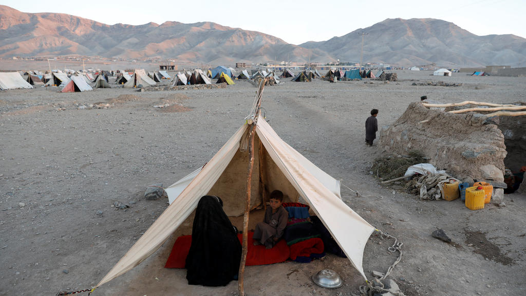 Internally displaced Afghan family sits inside a tent at a refugee camp in Herat province, Afghanistan October 14, 2018. Picture taken October 14, 2018. REUTERS/Mohammad Ismail
