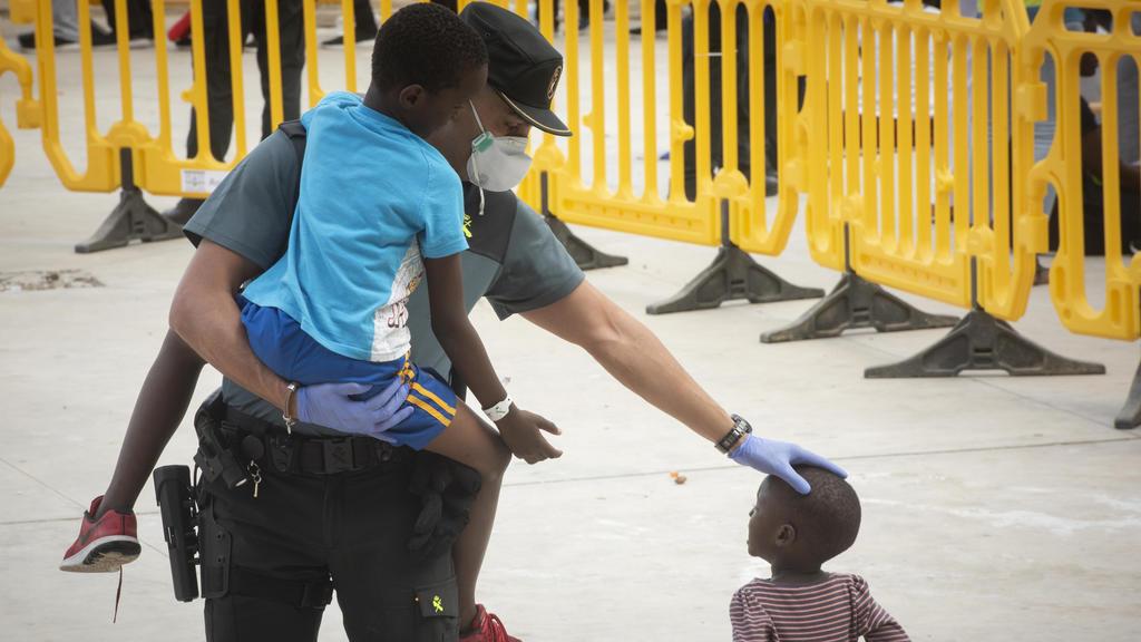 ARCHIV - 01.08.2018, Spanien, Los Barrios: Ein Beamter der Guardia Civil trägt ein Flüchtlingskind in einem Sportzentrum in Los Barrios, Südspanien, nachdem ed am Mittwoch, dem 1. August 2018, vom spanischen Rettungsdienst in der Straße von Gibraltar