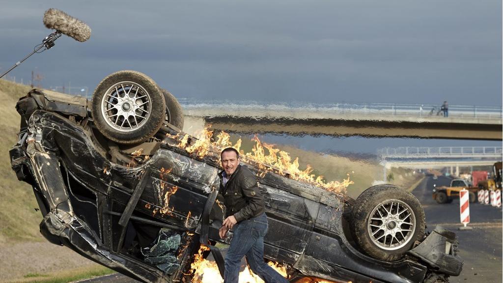 Semir Gerkhan alias Erdogan Atalay vor einem brennenden Auto.