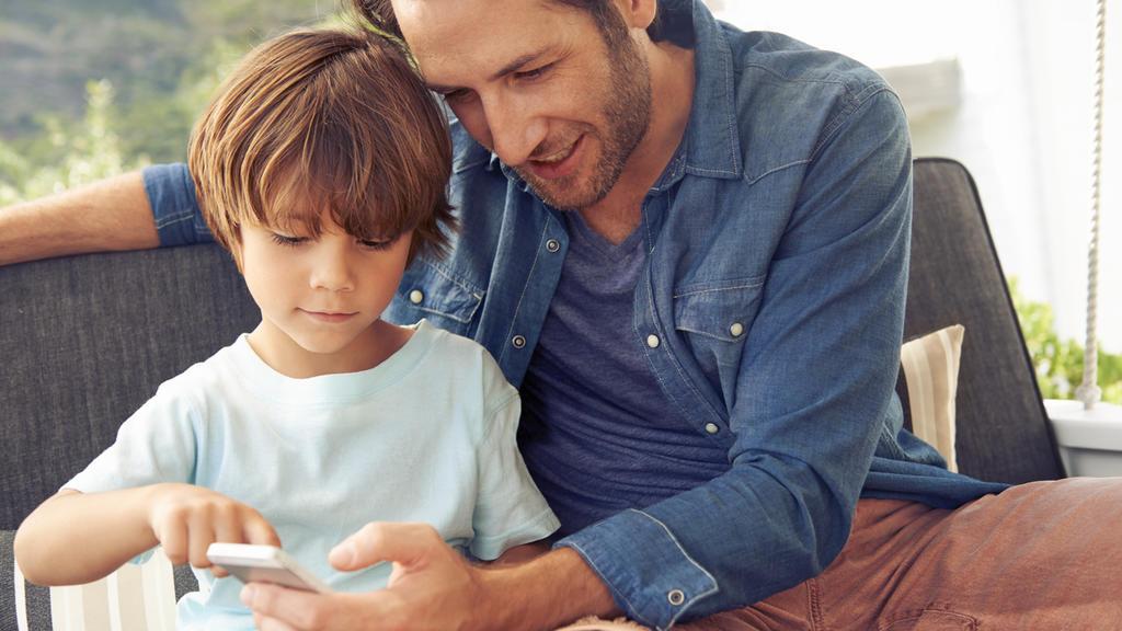 Ein Vater erklärt seinem Sohn das Smartphone.