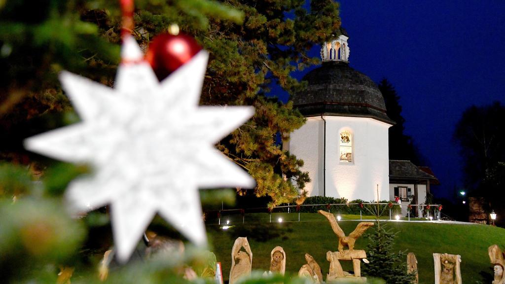 23.11.2018, Österreich, Oberndorf: Ein Weihnachtsstern mit den Noten zum möglicherweise bekanntesten Weihnachtslied der Welt hängt vor der Stille Nacht-Kapelle in Oberndorf bei Salzburg. 2018 feiert ·Stille Nacht! Heilige Nacht!· seinen 200. Geburtst