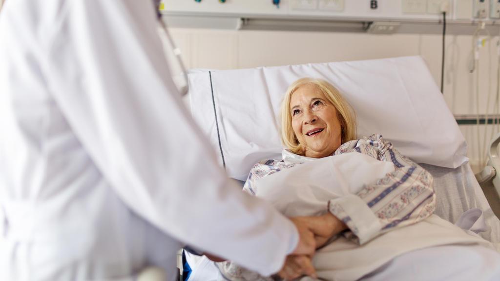 Eine Patientin im Krankenhaus im Gespräch mit einem Arzt.