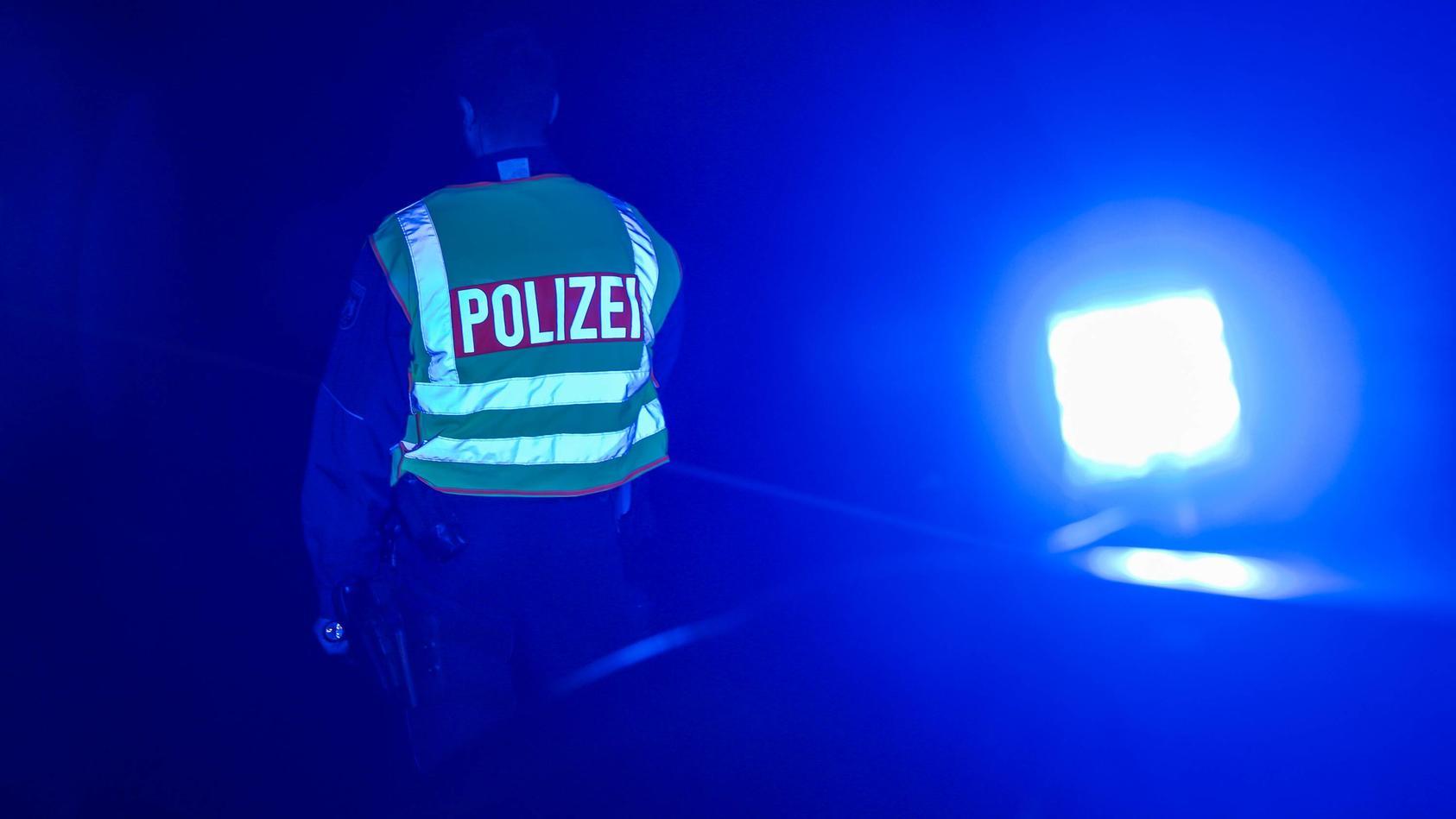 Ein Polizist in Uniform und mit Warnweste steht vor seinem Zivilfahrzeug mit aufgesetztem Blaulicht