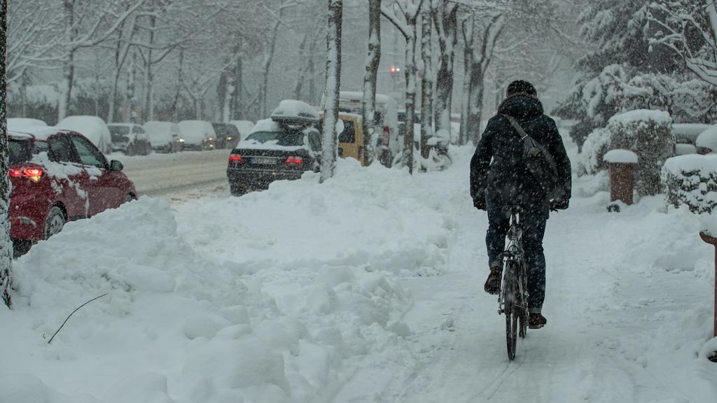 Starker Schneefall in München, Trotz hohem Schnne fährt hier ein Mensch mit dem Fahrrad. Weiterhin schneit es in München. Viele Straßen sind komplett weiß. München Bayern Deutschland Schwabing *** Heavy snowfall in Munich In spite of high snowfall, a