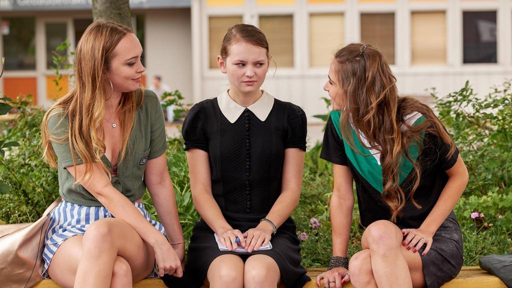Melanie (Mascha von Kreisler, l.) und Dunja (Cosima Henman, r.) sind von Lunas (Greta Bohacek) Asperger Autismus fasziniert und möchten mit ihr befreundet sein.