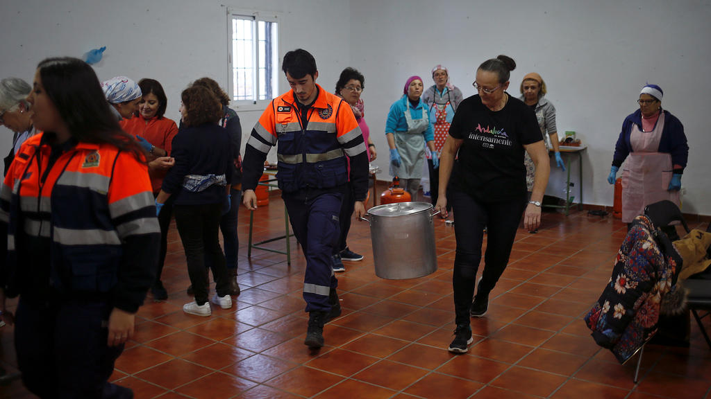 A member of Civil Protection and a volunteer carry a pot with food for the rescue personnel at the area where Julen, a Spanish two-year-old boy, fell into a deep well eight days ago when the family was taking a stroll through a private estate, in Tot