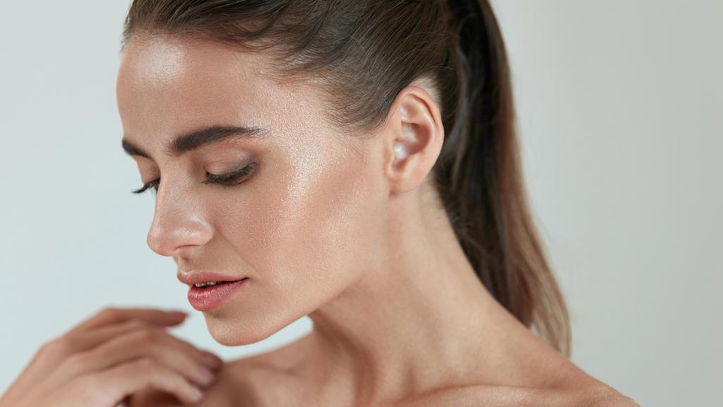 Junge Frau mit Make-up und Highlighter-Pude für frisch aussehende Haut
