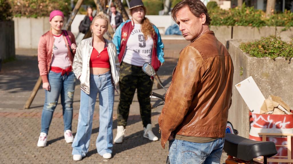Vollmer (Hendrik Duryn) stattet Maxi (Kyra Kahre, 2.v.l.) und ihren Mädels (Anika Lamade, Julia Jendroßek, r.) einen Besuch in ihrem Viertel ab - in einer Kölner Brennpunktgegend.