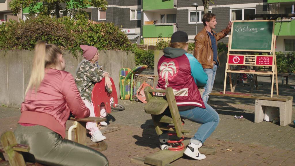 """""""Der Lehrer"""" Stefan Vollmer (Hendrik Duryn) unterrichtet die Schulverweigerer einfach auf dem Spielplatz."""