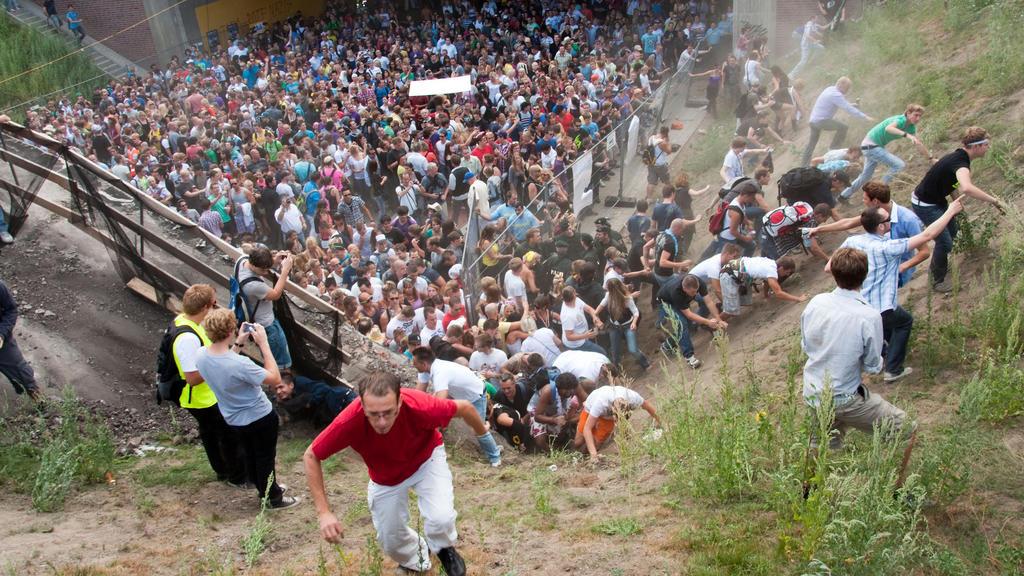 ARCHIV - 24.07.2010, Nordrhein-Westfalen, Duisburg: Tausende Raver drängen sich auf der Loveparade in und vor dem Tunnel in Duisburg, in dem sich eine Massenpanik ereignet hat. Am Dienstag findet in Düsseldorf der 100. Verhandlungstag im Loveparade-S