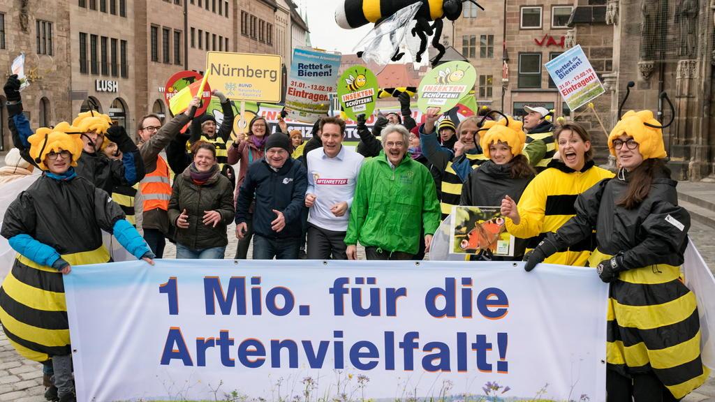 Agnes Becker (ÖDP, M,l-r), Norbert Schäffer (LBV), Ludwig Hartmann (Bündnis 90/Die Grünen) und Richard Mergner (Bund Naturschutz) stehen zusammen mit Unterstützern des Volksbegehrens