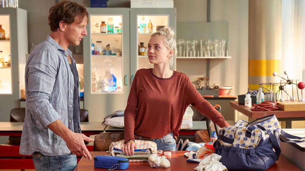 Die 16-jährige Mutter Lea (Louise Sophie Arnold) räumt nach einem anstrengenden Schultag ihre Sachen zusammen. Vollmer (Hendrik Duryn) hilft ihr dabei.