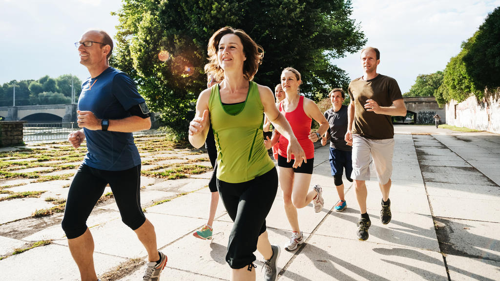 A group of amateur athletes out for a jog in the city, training together in the afternoon sun.