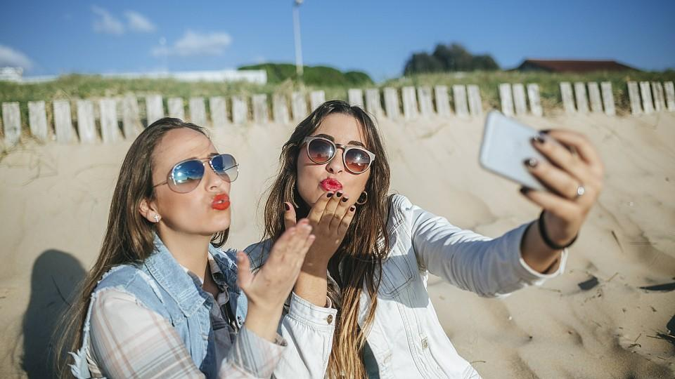 Two young women taking selfie on the beach while blowing a kiss model released Symbolfoto PUBLICATIONxINxGERxSUIxAUTxHUNxONLY KIJF01308Two Young Women Taking Selfie ON The Beach while blowing a Kiss Model released Symbolic image PUBLICATIONxINxGERxSU