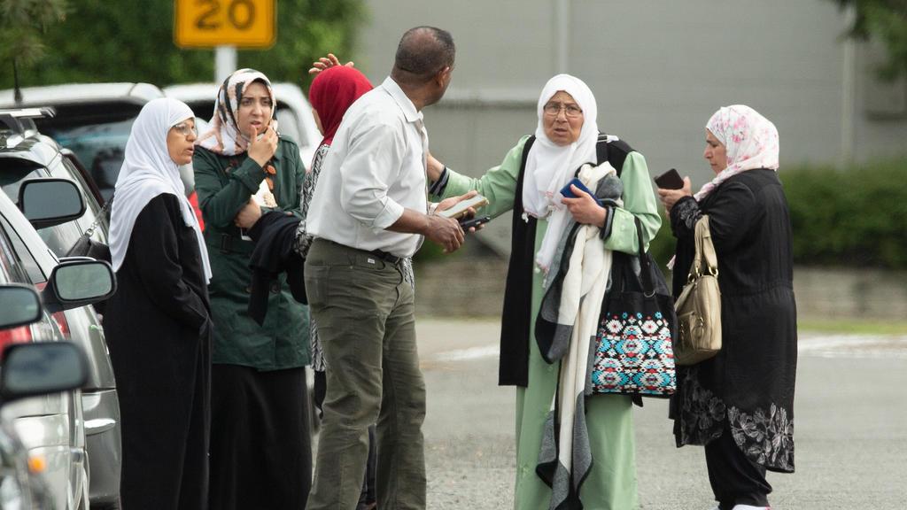 15.03.2019, Neuseeland, Christchurch: Menschen stehen nach Schüssen vor der Masjid Al Noor Moschee. Bei Angriffen auf zwei Moscheen in der neuseeländischen Stadt Christchurch sind am Freitag mehrere Menschen getötet worden. Foto: Martin Hunter/SNPA/d