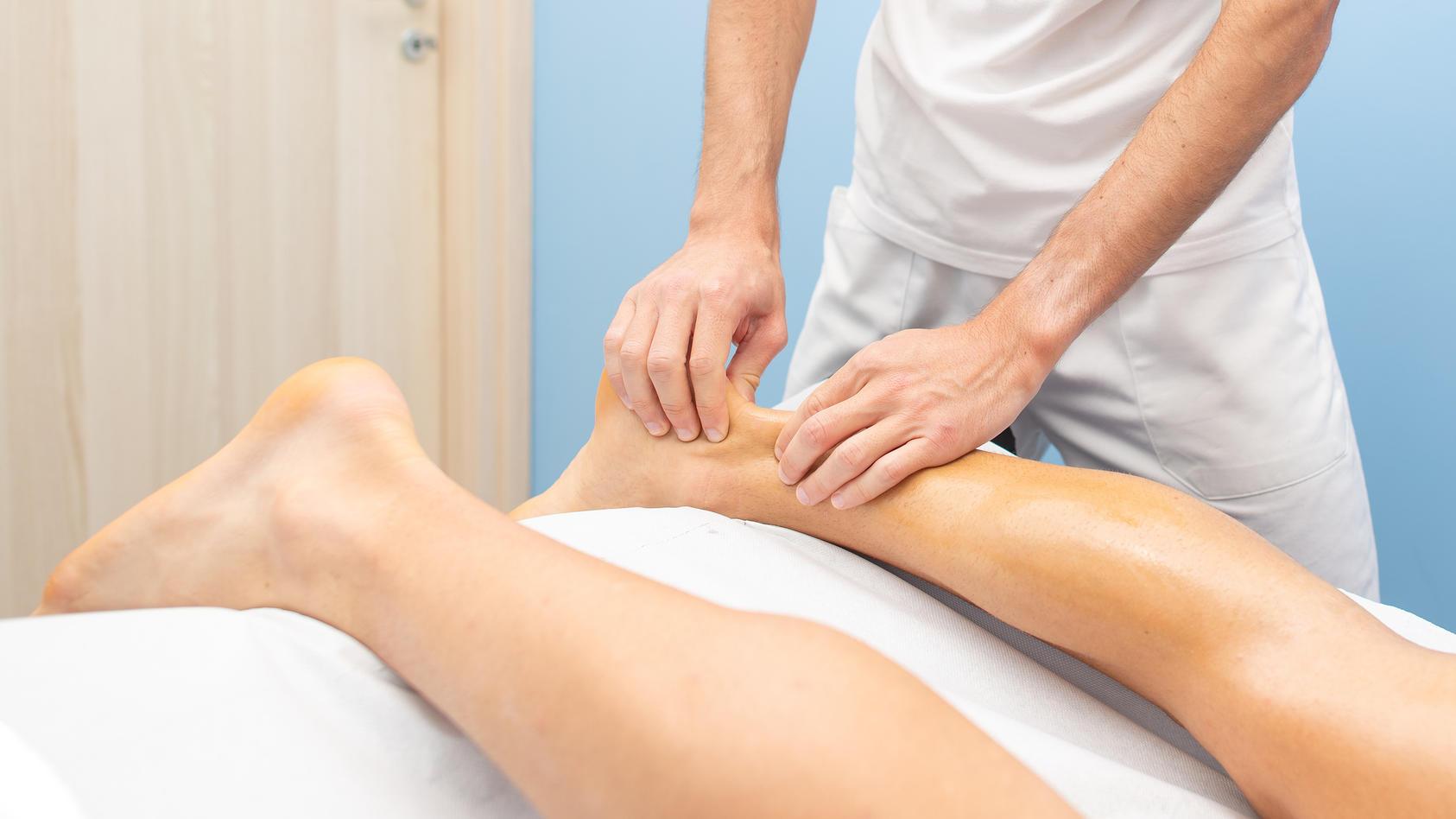 Physiotherapeut während einer Behandlung der Achillessehne
