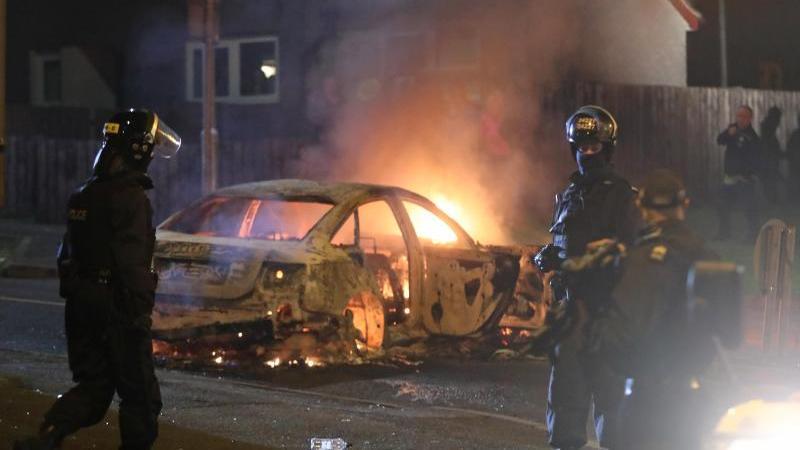 Polizisten vor einem brennenden Auto. Foto: Niall Carson/PA Wire