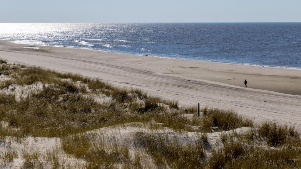 08.04.2019, Schleswig-Holstein, Wenningstedt/Sylt: Ein Mann läuft bei strahlendem Sonnenschein auf der Insel Sylt über einen ansonsten menschenleeren Strand Foto: Axel Heimken/dpa +++ dpa-Bildfunk +++