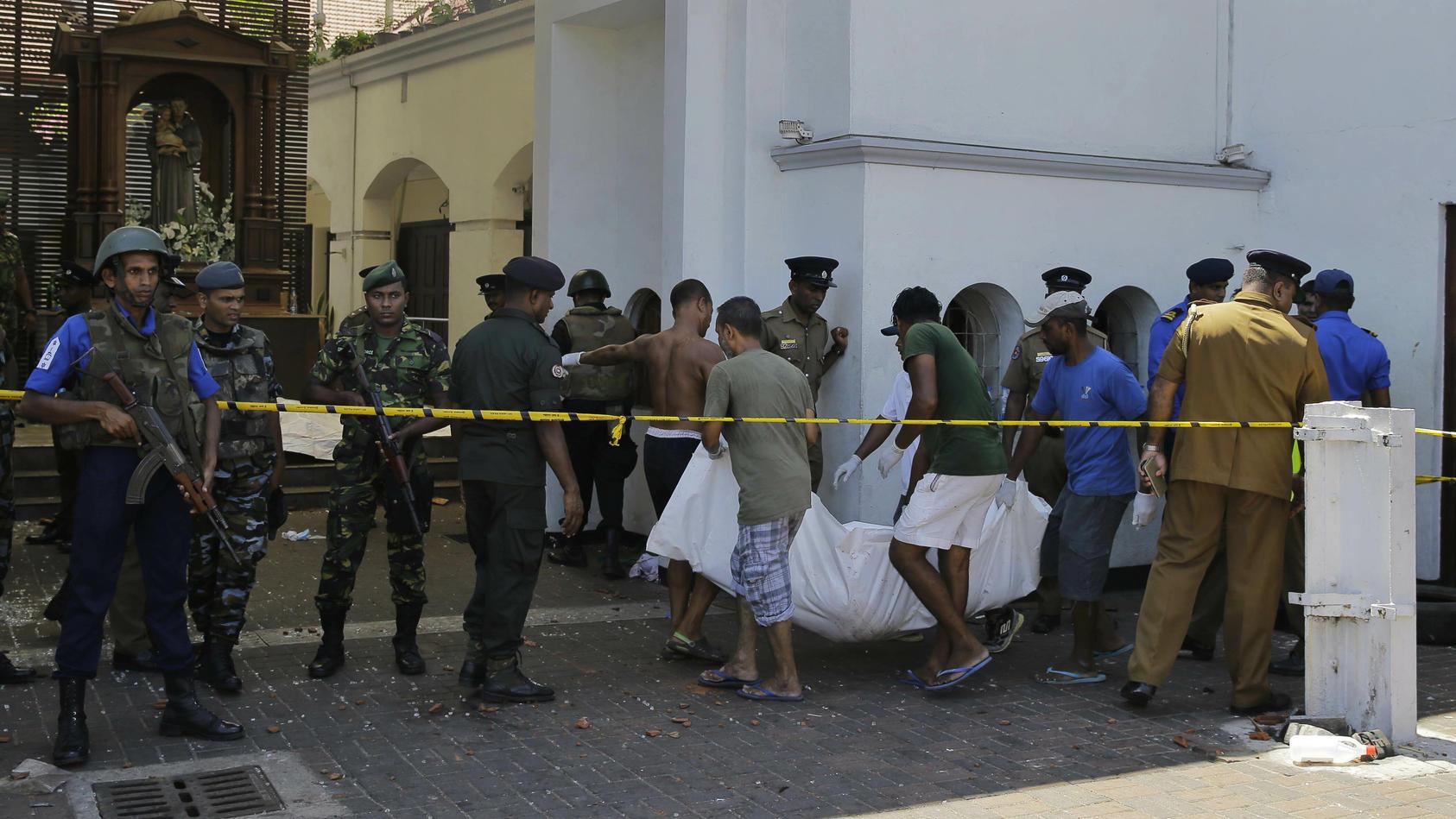 Zwischen Soldaten und Polizisten wird ein Leichnam aus der St.-Antonius-Kirche in Colombo getragen.