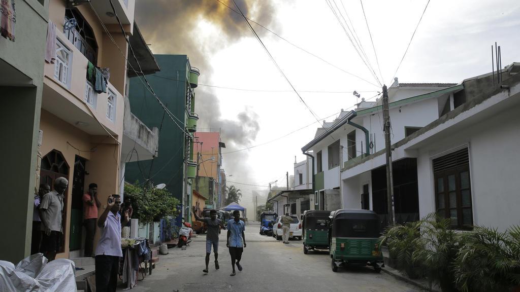 22.04.2019, Sri Lanka, Colombo: Menschen gehen auf einer Straße, während im Hintergrund Rauch aufsteigt. Am Ostermontag fand die Polizei weitere Sprengsätze in einem in der Nähe gesparkten Fahrzeug. Foto: Eranga Jayawardena/AP/dpa +++ dpa-Bildfunk ++