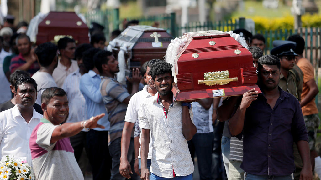 Coffins of victims are carried during a mass for victims, two days after a string of suicide bomb attacks on churches and luxury hotels across the island on Easter Sunday, in Colombo, Sri Lanka April 23, 2019. REUTERS/Dinuka Liyanawatte