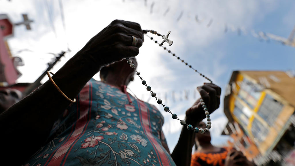 A woman holds a rosary as silence is observed as a tribute to victims, two days after a string of suicide bomb attacks on churches and luxury hotels across the island on Easter Sunday, during a memorial service in Colombo April 23, 2019. REUTERS/Dinu