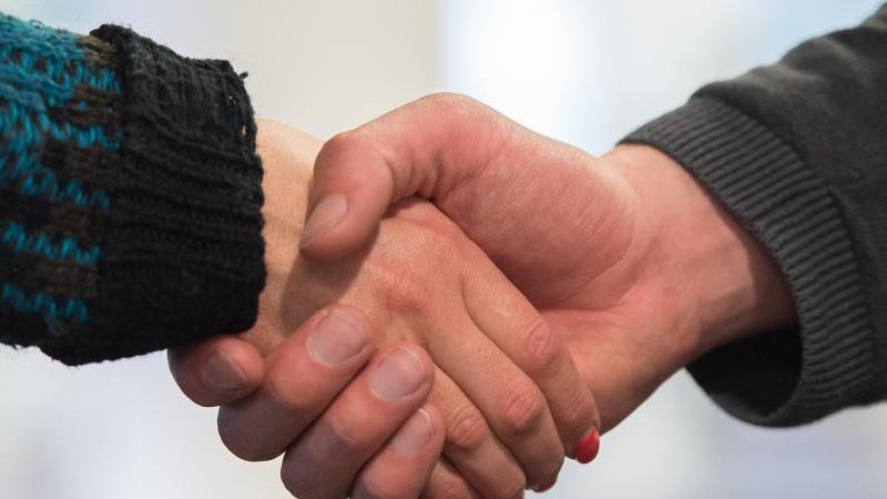 Ein Mann und eine Frau begrüßen sich mit Handschlag. Foto: Silas Stein/Archivbild