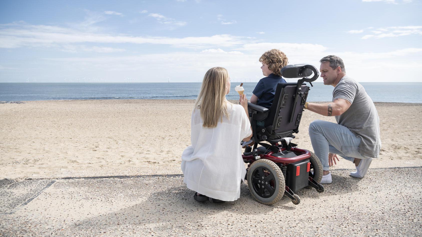Behindertes Kind mit Eltern am Strand