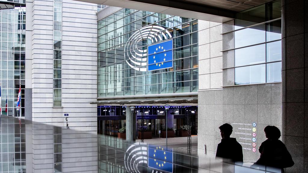 26.05.2019, Belgien, Brüssel: Ein Eingang zum Europäischen Parlament spiegelt sich in einer Glasfläche. Vom 23.05. bis 26. Mai wählen die Bürger von 28 EU-Staaten ein neues Parlament. Foto: Marcel Kusch/dpa +++ dpa-Bildfunk +++