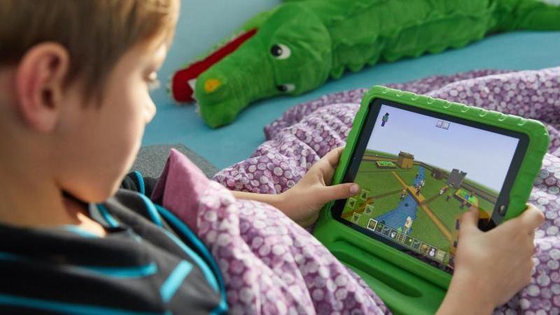 Ein Junge spielt auf einem Ipad das Open-World-Computerspiel Minecraft.