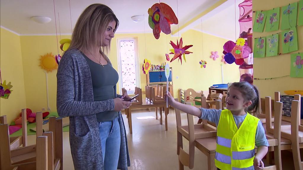 """Elisa und ihre Mutter finden die Idee gut, dass Eltern in Kitas die Handys weg lassen. Töchterchen zeigt ihrer Mutter die """"Handy-weg""""-Kelle"""