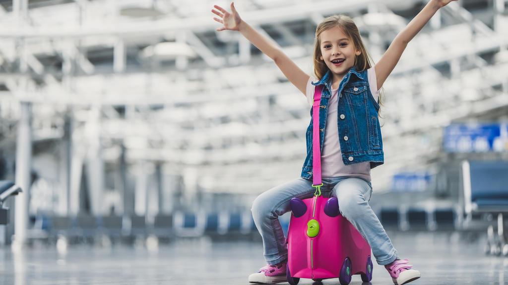 Das Gepäck ist aufgegeben und das kleine Mädchen ist bereit, mit seinem Handgepäck, den Flieger zu besteigen