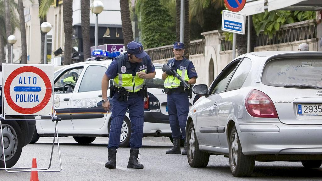 Spanish National Police officers inspect cars at a roadblock in downtown Palma de Mallora, Balearic Islands on 10 August 2009, one day after three small bombs exploded in places frequented by tourists in the capital of the island of Mallorca. Few clu