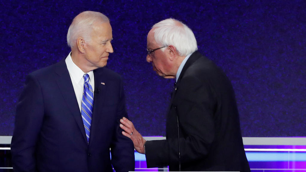 Former Vice President Joe Biden talks with Senator Bernie Sanders in the midst of a commercial break during the second night of the first Democratic presidential candidates debate in Miami, Florida, U.S. June 27, 2019. REUTERS/Mike Segar     TPX IMAG