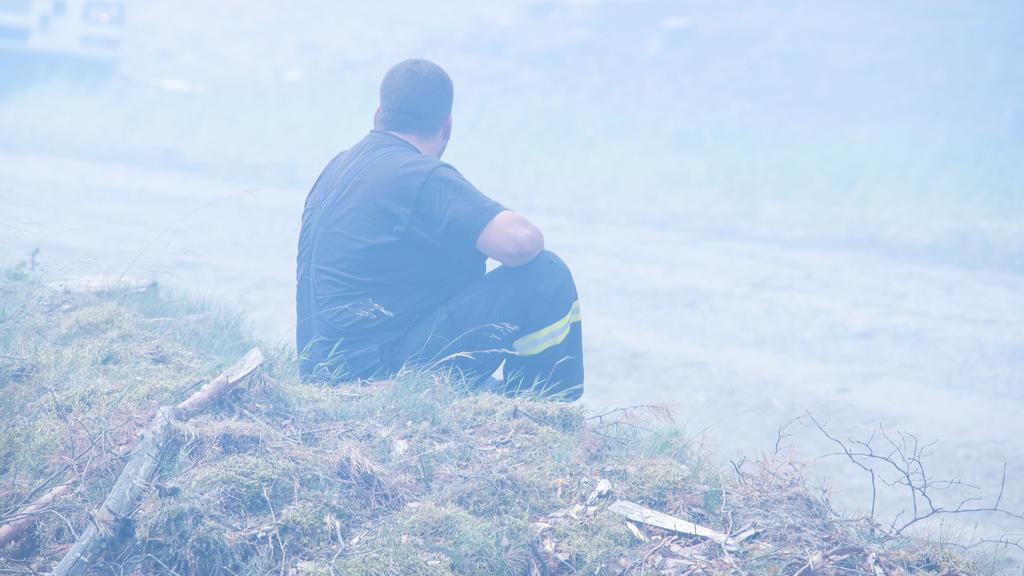 01.07.2019, Mecklenburg-Vorpommern, Alt Jabel: Ein erschöpfter Feuerwehrmann sitzt in einer Rauchwolke im brennenden Wald in der Nähe der kleinen Ortschaft Alt Kabel am Rande des ehemaligen Truppenübungsplatzes bei einem großflächigen Waldbrand in de