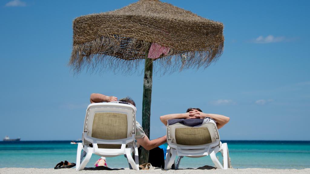 ARCHIV - 09.06.2013, Spanien, Muro: Deutsche Urlauber liegen an einem Strand im Norden der Mittelmeerinsel Mallorca. Millionen Bundesbürger sind so arm, dass sie sich keine Urlaubsreise leisten können. Etwa jeder Siebte konnte im vergangenen Jahr nic